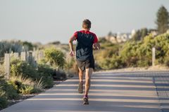 Back portrait of young sport runner man with fit and strong healthy body training on off road track in Summer running workout. Back portrait of young attractive Stock Images
