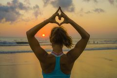 Back portrait of young fit and healthy attractive woman doing love heart shape with hands and fingers against amazing beautiful su. Nset beach in yoga meditation royalty free stock photography