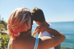 Young woman leaning on her boyfriend looking at sea. Back portrait of young women leaning on her boyfriend looking at sea Stock Photo