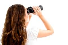 Back pose of female holding binocular Royalty Free Stock Images
