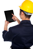 Back pose of worker operating tablet device. Young construction worker operating touch pad device Stock Photography