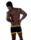 Back pose of young fit male trainer. Hands on his waist Royalty Free Stock Photography