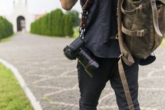 Back of professional wedding photographer in black shirt and with a two cameras an a shoulder straps and brown bag stock images