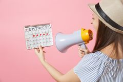 Back rear view angry woman screaming in megaphone, holding periods calendar for checking menstruation days isolated on stock images