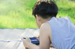 Back rear view-Asian boy with cute, with looking tablet in hand, online learning concepts and e-learning with learning outside stock photo
