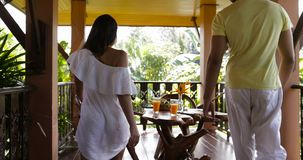 Back Rear View Of Couple Walking To Summer Terrace Sit At Table Young Man And Woman Diverse Having Breakfast Talking stock video footage