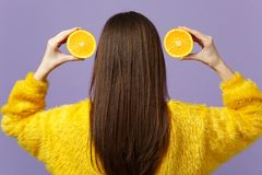Back Rear View Of Young Woman In Fur Sweater Holding Halfs Of Fresh Ripe Orange Fruit Near Hair Isolated On Violet Stock Photos