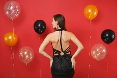 Back rear view of young woman in little black dress looking aside, celebrating on bright red background air