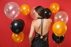 Back rear view of tender young woman in little black dress celebrating on red background air balloons. St. Valentine`s