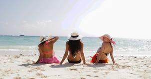 Back rear view of three girls on beach in bikini, enjoy sun tan talking, woman taking off straw hats tourists on summer stock footage