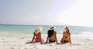 Back rear view of three girls on beach in bikini and straw hats enjoy sun tan talking, woman tourists on summer holiday stock video footage