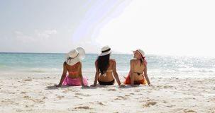Back rear view of three girls on beach in bikini and straw hats enjoy sun tan, woman tourists group on summer holiday stock footage