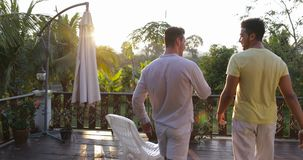 Back Rear View Of Two Men Walking Out On Summer Terrace Talking, Gay Couple Diverse Communicating Over Sunset In. Tropical Forest Slow Motion 60 stock video