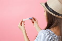 Back rear view woman in blue dress, hat hold in hand, looking at pregnancy test isolated on pink background. Medical. Excited happy woman in blue dress, hat hold stock images