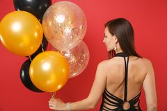 Back rear view of young girl in little black dress celebrating looking aside holding air balloons isolated on red