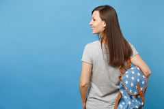 Back rear view of young smiling brunette woman student in casual clothes with backpack looking aside isolated on blue royalty free stock photos