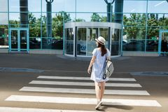 Back rear view of young smiling traveler tourist woman in hat with backpack standing on crosswalk at international stock image