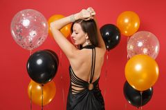 Back rear view of young woman in black dress celebrating, rising hands, looking aside on bright red background air