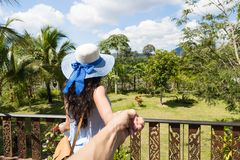 Back Rear View Of Young Woman In Hat Over Beautiful Tropical Landscape Holding Man Hand Stock Photography