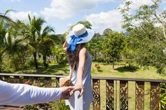 Back Rear View Of Young Woman In Hat Over Beautiful Tropical Landscape Holding Man Hand Royalty Free Stock Images