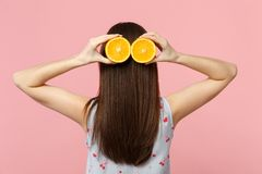 Back rear view of young woman in summer clothes hold halfs of fresh ripe orange fruit near hair isolated on pink pastel. Background. People vivid lifestyle stock image