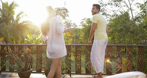 Back Rear View Of Young Woman Walk On Summer Terrace With Juice To Man Looking At Sunset Landscape Over Tropical Forest stock video