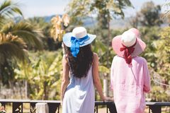Back Rear View Of Young Women Couple Wearing Hats Over Beautiful Tropical Landscape. On Balcony Or Summer Terrace Stock Photo