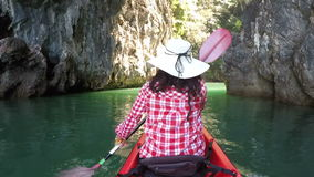 Back rear of woman kayaking in beautiful lagoon action camera view of girl paddling on kayak boat. In sea caves stock footage