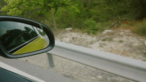 Back road reflected in car mirror, car driving fast stock video footage
