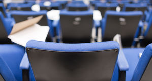 Back row perspective view of lecture chair. In conferences room Stock Photography