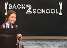 Back 2 school text on blackboard with with disabled girl in wheelchair. Digital composite of Back 2 school text on blackboard with with disabled girl in Royalty Free Stock Photo
