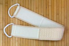 Back scrubbing soft towel strap to rub exfoliating skin during s. Hower with 2 rope to pull, on wooden background Stock Photography
