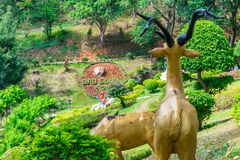 The back of sculpture of deer in a tropical park with flowers. The back of an artificial deer in a tropical park with flowers, animal, asia, asian, background stock photo