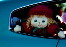 Back Seat Doll. A doll peeks out of a back seat window of a car Stock Photo