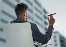Back of seated business man smoking cigar and looking at blurry building Stock Image