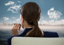 Back of seated business woman smoking cigar and looking at blurry skyline and water royalty free stock images