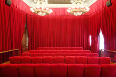 Back of seats in picture show hall. Back of red soft seats in picture show hall with red curtains and big luster Stock Photo