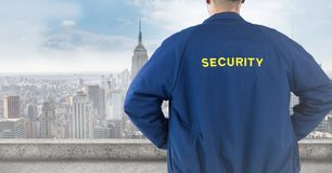 Back of security guard against blurry skyline. Digital composite of Back of security guard against blurry skyline stock image