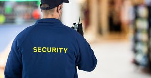 Back of security guard with walkie talkie against blurry shopping centre. Digital composite of Back of security guard with walkie talkie against blurry shopping royalty free stock photography