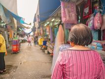 Back of Senior asian women walking and shopping on & x22;Phahurat & x22; Road the Old marketplace in Bangkok City. Capital of thailand stock photography