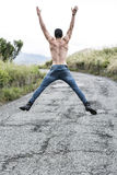 Back of shirtless fit young man jumping for joy Stock Image