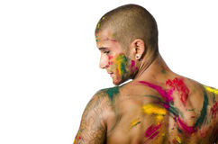 Back of shirtless young man, skin painted all over. Handsome young man seen from the back with skin all painted with Holi colors, isolated on white background Royalty Free Stock Images