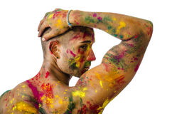 Back of shirtless young man, skin painted all over. Handsome young man seen from the back with skin all painted with Holi colors, isolated on white background Royalty Free Stock Image