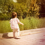 Back shot of little baby girl. First steps. Stock Images