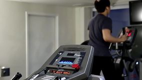 Back shot of man running on a treadmill in a gym stock video footage