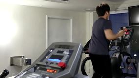 Back shot of man running on a treadmill stock footage