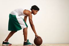 Back shot photo of basketball player holding the ball at his side on grunge background Royalty Free Stock Images