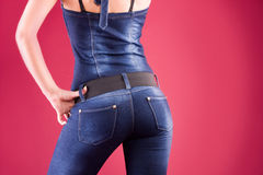 Back shot of pretty girl her jeans. Back and ass of beautiful woman over red background Royalty Free Stock Photography