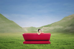 Back shot of red sofa with pensive woman outdoor Stock Image