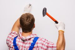 Back shot of repairman nailing Royalty Free Stock Images